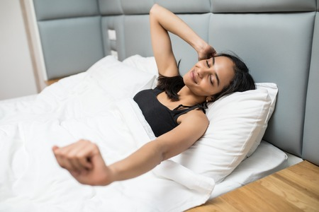 Photo for Happy girl waking up stretching arms on the bed in the morning - Royalty Free Image