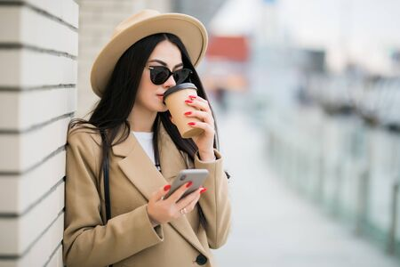 Young woman use phone while walking to work drinking coffee on morning commute in city