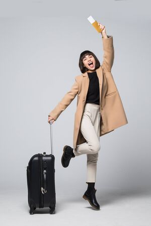 Photo pour Happy young woman tourist jumping, holding suitcase and passport, flight tickets, isolated on white background - image libre de droit