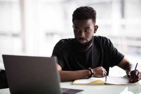 Photo for Image of young African man looking at camera with laptop near by - Royalty Free Image