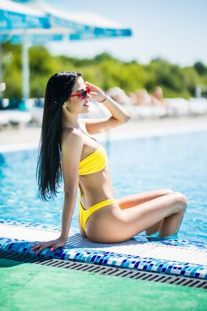 Photo pour Attractive young woman in bikini relaxing at the poolside. Woman sitting by a swimming pool looking at camera and smiling. - image libre de droit