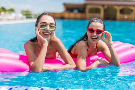 Photo pour Two girls are swimming in a pool on inflatable mattresses - image libre de droit