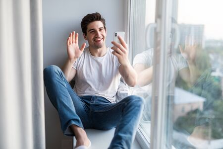 Photo pour Young man sitting on the windowsill make video call on the phone - image libre de droit
