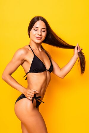 Photo for Young woman in black swimsuit posing against yellow background. - Royalty Free Image