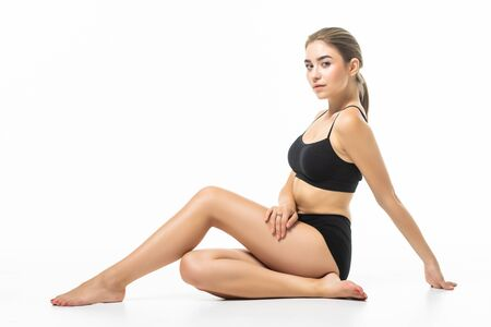Photo pour Feeling satisfied. Girl with perfect slim toned young body sitting in the studio with white background behind. - image libre de droit