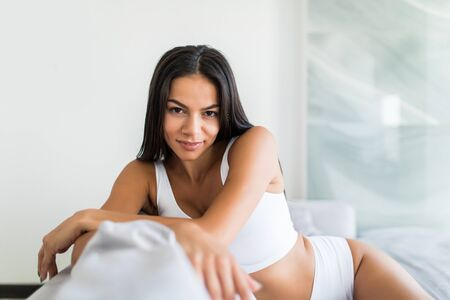 Photo pour Beautiful young woman in lingerie looking at camera sitting on couch at home - image libre de droit
