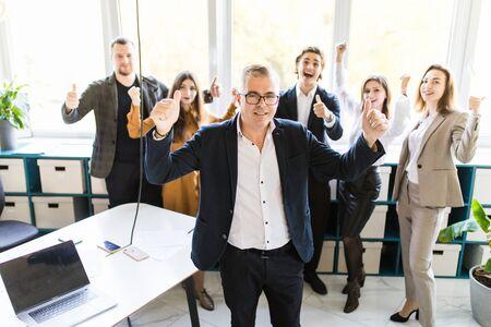 Foto de Happy businessman with win gesture standing in front of his colleagues in office - Imagen libre de derechos
