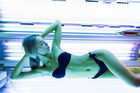 Photo pour young woman at laying on solarium bed and get brown skin tone - image libre de droit