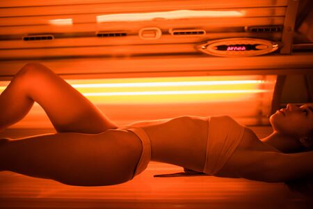 Photo pour young woman at laying on solarium bed and get brown skin tone ready for summer - image libre de droit