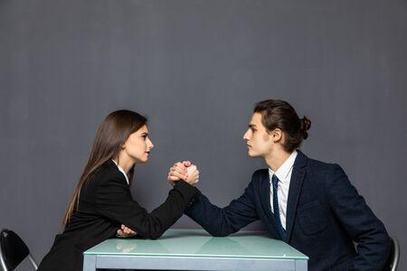 Photo pour Beautiful business couple doing arm wrestling challenge on gray background - image libre de droit