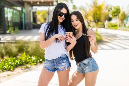 Photo pour Two womens watching media content online in a smart phone outdoors - image libre de droit