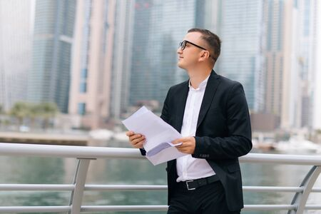 Photo pour Handsome young man in suit reading contract while standing outdoors - image libre de droit