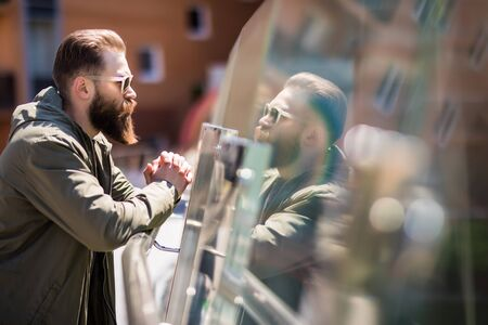 Photo for Handsome bearded man in sunglasses is looking at camera while standing on balcony - Royalty Free Image