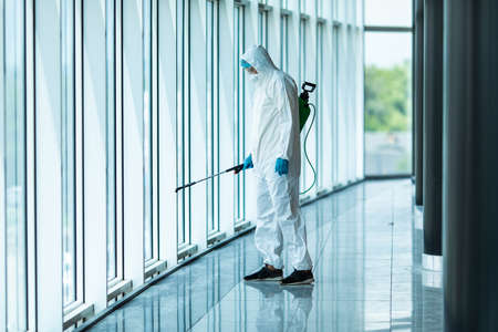 Photo for Coronavirus Pandemic. A disinfector in a protective suit and mask sprays disinfectants in the office. Protection agsinst COVID-19 disease. Prevention of spreding pneumonia virus with surfaces. - Royalty Free Image
