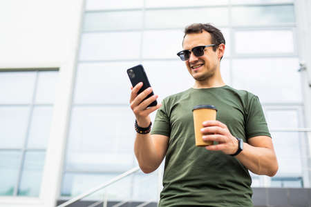 Photo pour Happy male standing and looking at cup with joy holding mobile and enjoying leisure in city - image libre de droit