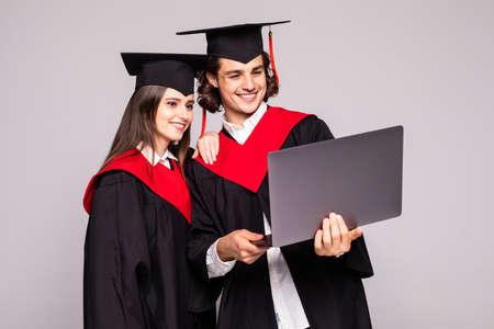 Photo pour Young graduation couple holding laptop isolated on white background - image libre de droit