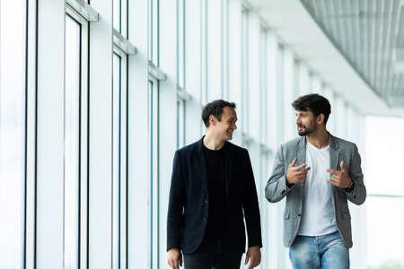 Photo pour Portrait of two concentrated businessmen partners dressed in formal suit walking and having conversation - image libre de droit
