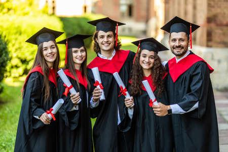 Photo pour Close-up of five graduates posing in front of the university - image libre de droit