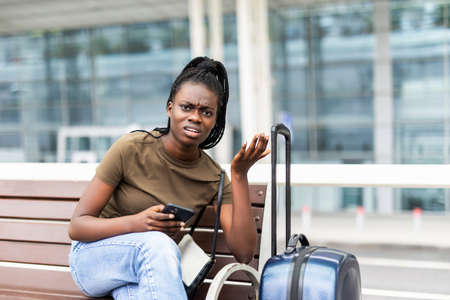 Photo pour Sad african woman with suitcase in airport waiting flight. - image libre de droit