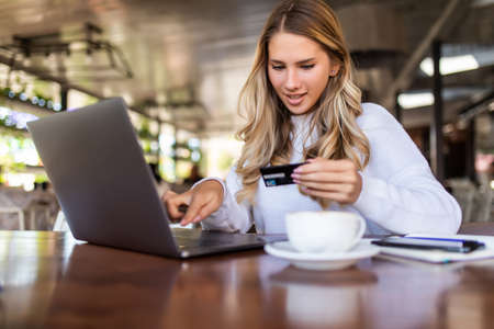 Photo pour Happy woman using credit card and laptop for shopping while sitting in cafe. - image libre de droit