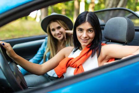 Photo pour Two Female Friends On Road Trip Driving In Convertible Car - image libre de droit