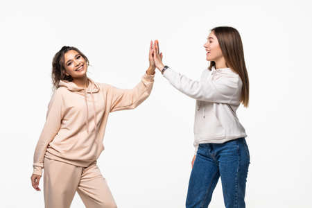 Photo for Portrait of two attractive mixed race women laughing and giving high five over white background - Royalty Free Image