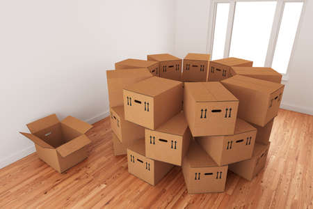 Arrangement of empty cardboard packing boxes standing on a wooden floor in a room interior.