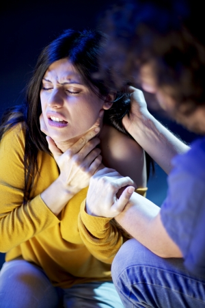 man strangling and holding hair of woman in pain domestic violence