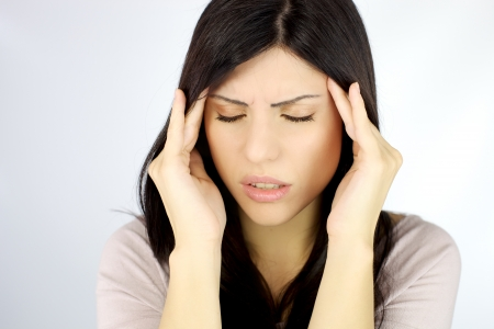 Depressed young woman with terrible headache touching head with hands