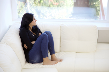 Photo for pretty alone brunette woman looking outside lost in her thoughts - Royalty Free Image
