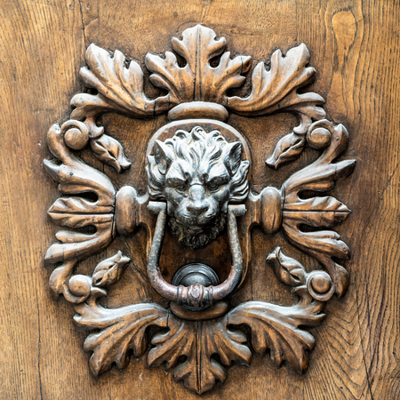Foto per ancient metal handle of a wooden door of a midieval city. Object with a dark appearance - Immagine Royalty Free