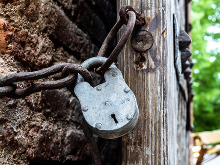 Foto per closed metal padlock and chain on the wooden entrance door of a medieval city. Dark appearance - Immagine Royalty Free