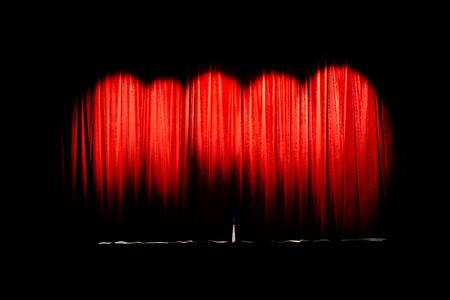 Red curtain of movie theater closed illuminated by 5 spot lights