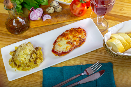 Chicken Parmigiana and spaghetti close up on a plate on the table.