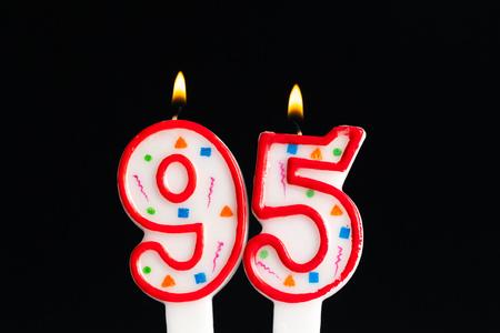 Foto de Colorful burning birthday candle  on dark background - Imagen libre de derechos