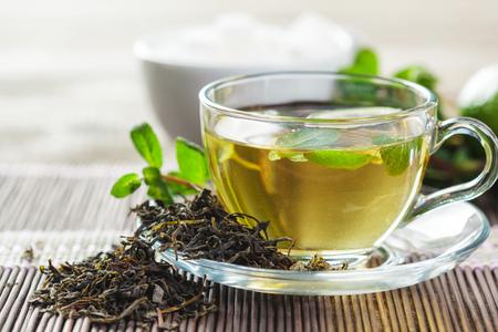 Photo pour cup of black tea with mint leaves on a wooden table - image libre de droit