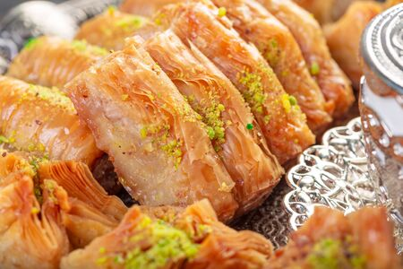 Photo pour Turkish arabic dessert baklava with honey and nuts on a silver plate. Close up. - image libre de droit
