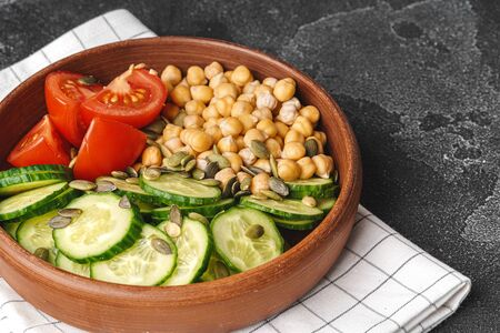 Foto für Clay plate of chickpeas and cut cucumbers and tomatoes. Healthy eating - Lizenzfreies Bild