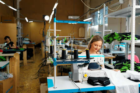 Photo pour Seamstress woman at her workplace sewing clothes on sewing machine - image libre de droit