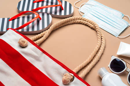 Photo pour Beach bag with beach items and protective mask on beige background. Coronavirus summer concept - image libre de droit