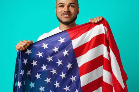 Portrait of young dark-skinned man proudly holding USA flag