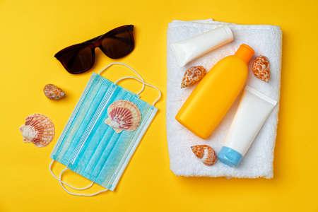 Photo pour Sunscreen cream and protective mask. Coronavirus summer concept - image libre de droit