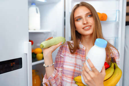 Photo for Portrait of a young blonde woman taking food from her fridge - Royalty Free Image