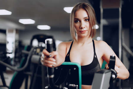 Photo for Young beautiful woman training her arms in a gym apparatus - Royalty Free Image