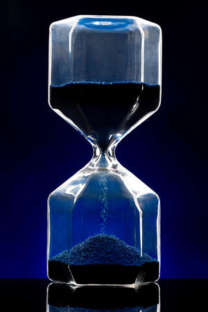 Photo pour Hourglass illuminated on dark blue background close up - image libre de droit