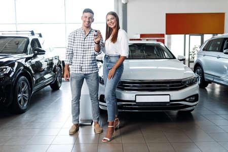 Photo pour Young happy couple just bought a new car in a dealership - image libre de droit