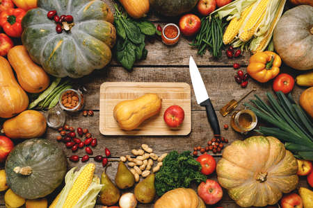 Photo for Wooden cutting board with autumn vegetables on wooden table - Royalty Free Image