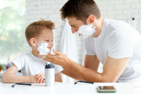 Photo for Father teaches his little son how to shave face - Royalty Free Image