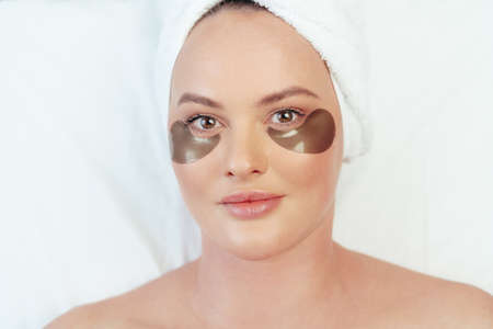 Photo pour Portrait of a woman lying in a spa beauty salon with eye patches applied and with towel on her head - image libre de droit