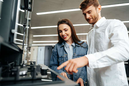Photo pour Young couple choosing new gas stove in home appliances store - image libre de droit